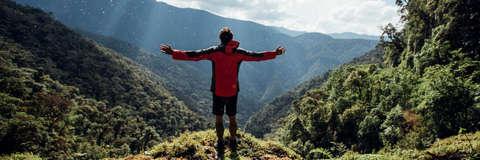Ein Mann trägt eine PFC freie Jacke von Jack Wolfskin. Er steht auf einem Berg und schaut mit zur Seite ausgebreiteten Armen in das grüne Tal.