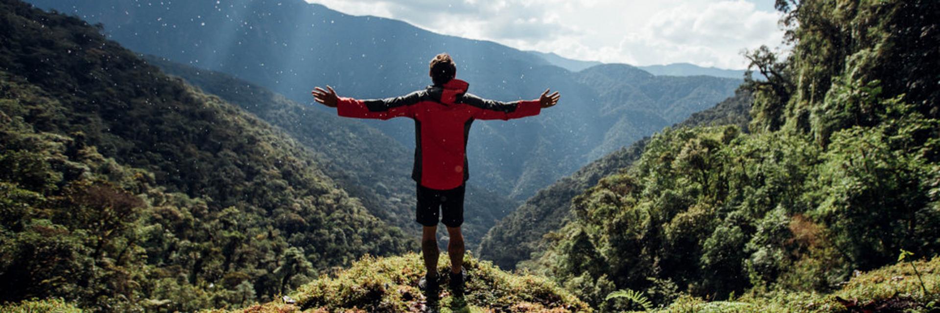 Ein Mann in Outdoorjacke steht vor einem Bergpanorama.