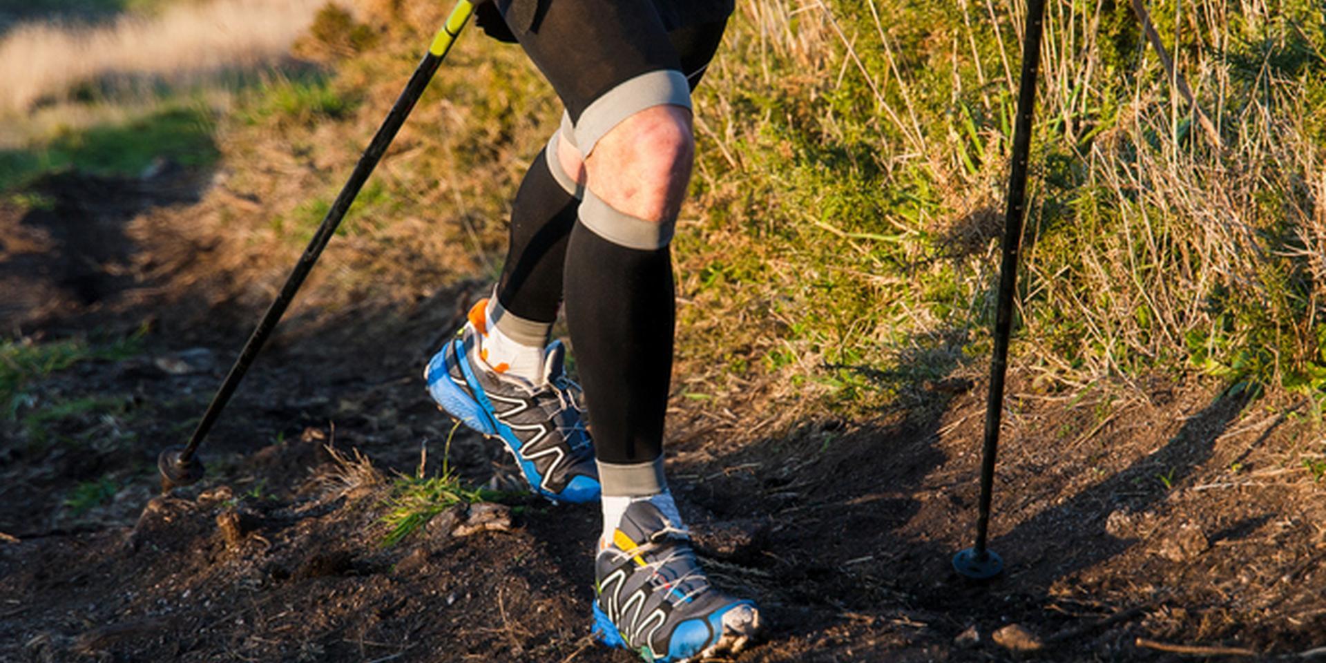 Ein Trailrunner läuft mit Trailrunning Stöcken in der Hand auf einem erdigen Trail.