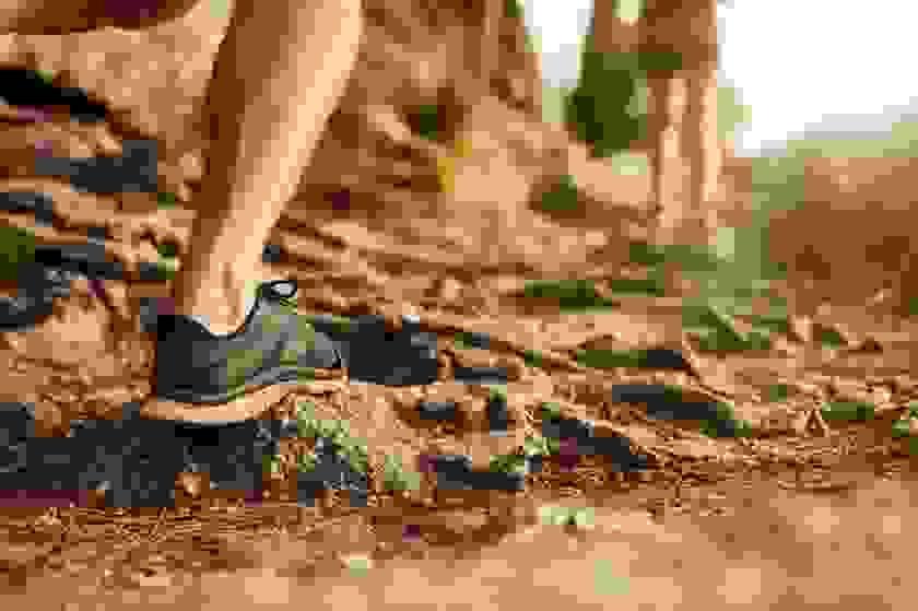 Der Schuh eines Trailrunners in Nahaufnahme während eines Laufs im Wald.