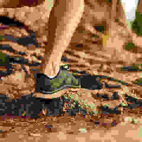 Dargestellt sind die Füße von Läufern beim Trailrunning auf unebenem Untergrund.
