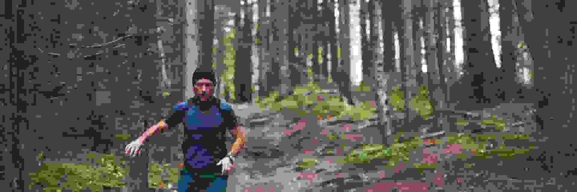 Ein Mann beim Trailrunning in einem Wald.
