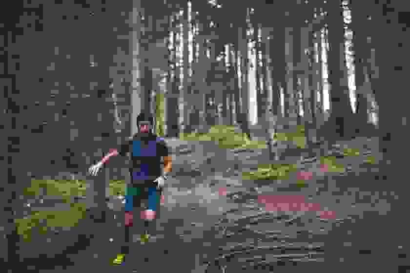Ein Mann läuft im Wald bergab.