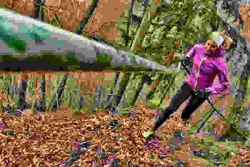 Eine Trailrunnerin in lila farbener Regenjacke erklimmt eine Steigung.