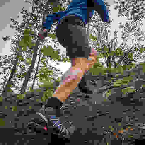 Ein Läufer rennt in Trailrunning Schuhen einen Erdhügel hinauf.