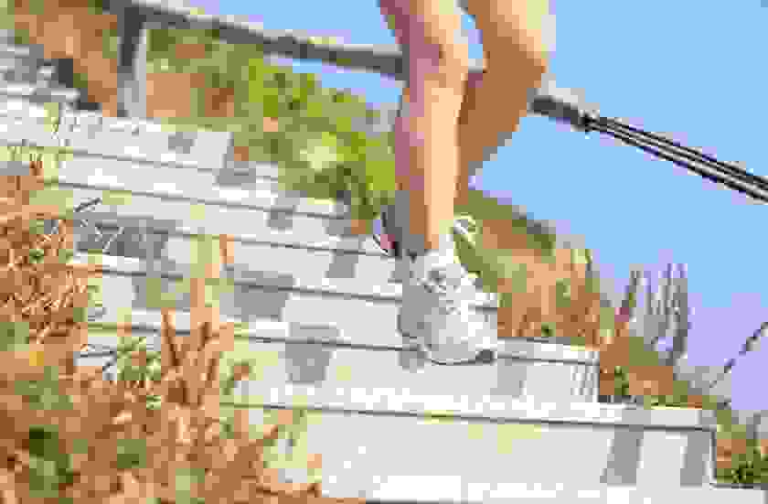 Die Beine einer Frau, die gerade in Laufschuhen eine Treppe hinab läuft.