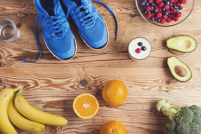 Auf einem Tisch sind blaue Laufschuhe und diverse Obstsorten arrangiert.
