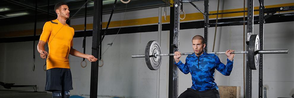 Zwei Männer trainieren in einem Fitnesstudio. Der eine macht Kniebeugen mit einer Langhantel, der andere macht Seilspringen.