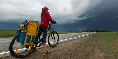 Eine Frau steht mit ihrem Fahrrad an einer Landstraße.