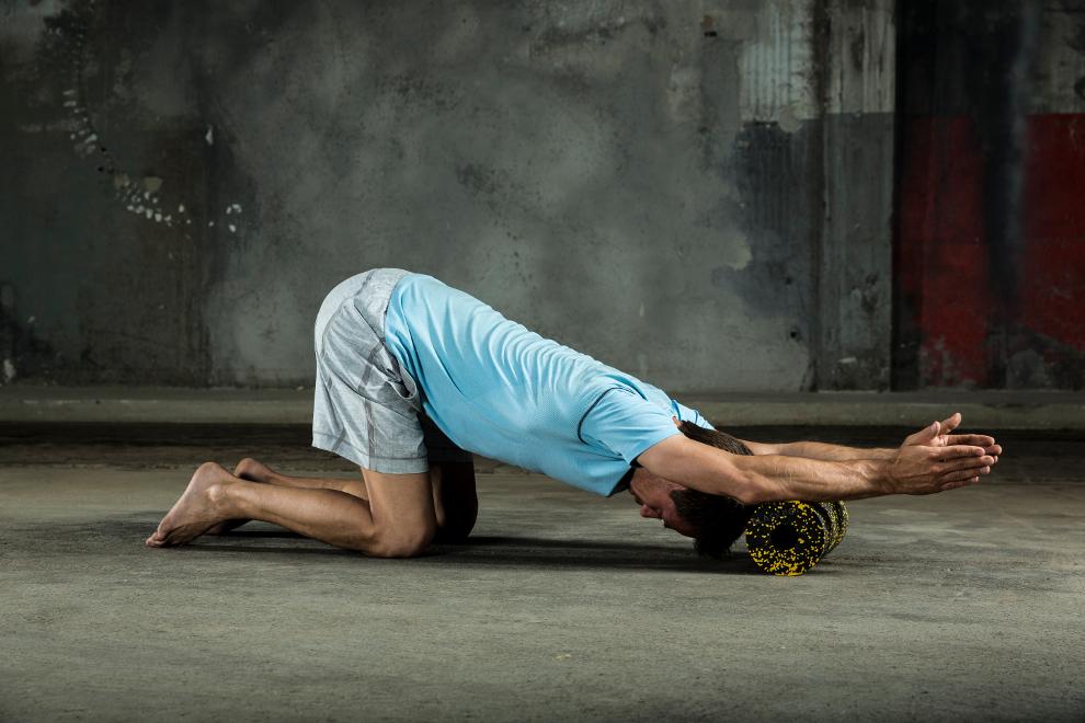 Ein Mann trainiert seine Unterarme mit einer Blackroll Faszienrolle.