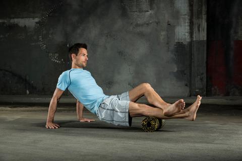Ein Mann massiert mit einer Faszienrolle seine Wade.