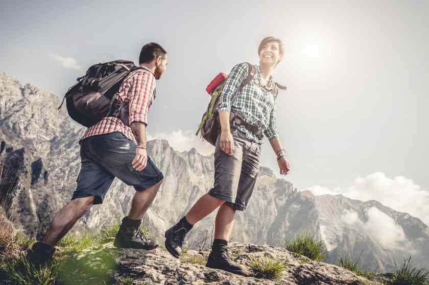 Ein Mann und eine Frau wandern in kurzen Wanderhosen durch ein Gebirge.