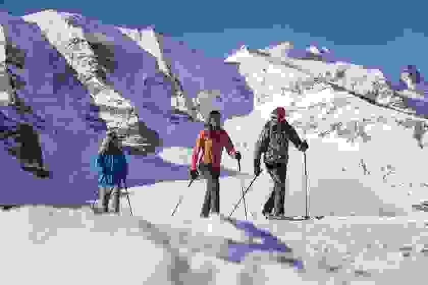 Eine schöne Winterlandschaft, die von 3 Schneewanderern durchwandert wird.