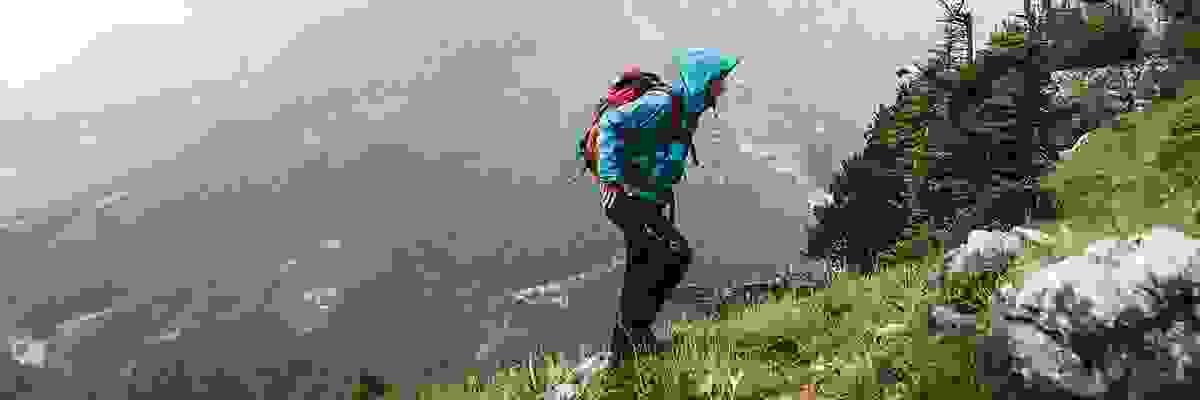 Ein Wanderer geht bei Regen über einen Wanderweg während er eine türkise Wanderjacke trägt