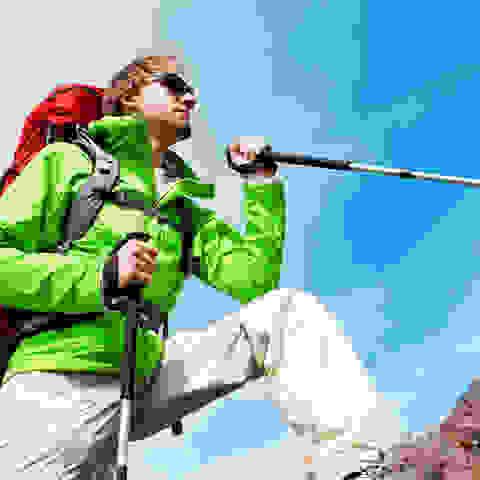 Ein Wanderer in grüner Wanderjacke mit rotem Rucksack, Sonnenbrille und Wanderstöcken erklimmt einen Gebirgsweg.