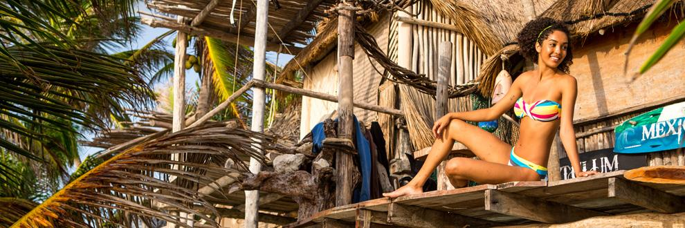 Eine Frau in einem Bikini auf einer Holzveranda.