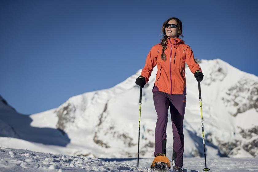 Eine Frau ist bei schönem Wetter im Gebirge beim Winterwandern mit Stöcken unterwegs.