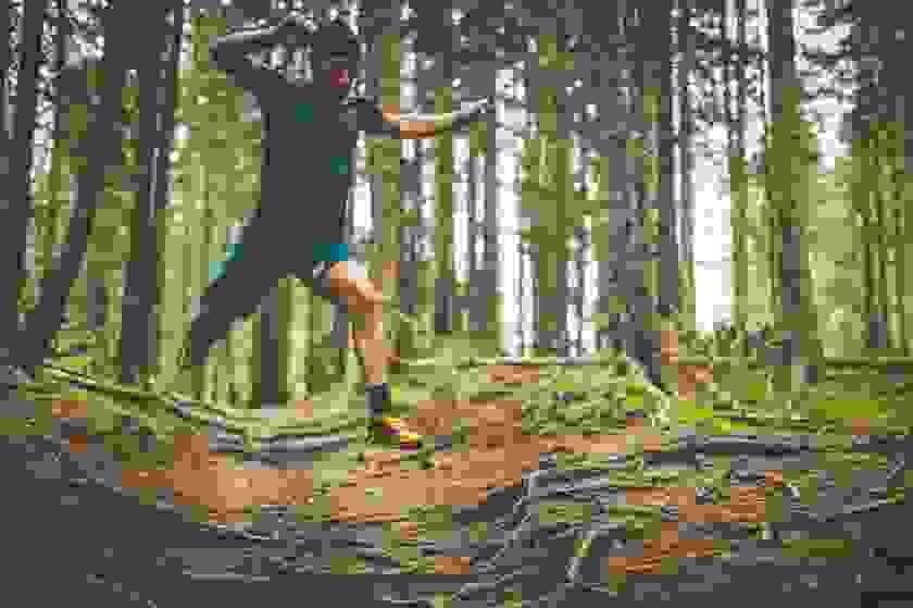 Ein Trailrunner springt über Baumwurzeln die auf einem Waldweg vorhanden sind.